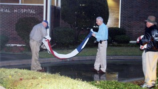 Photo courtesy of Bowie News Lynn Heller and Ernie Parisi, along with Don Marlow, fold the flags for last time at Bowie Memorial Hospital.